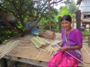 Outside, this husband and wife are cutting thin strips of bamboo in preparation for the rice harvest.  They will tie the bundles of rice and the rice bags with them.